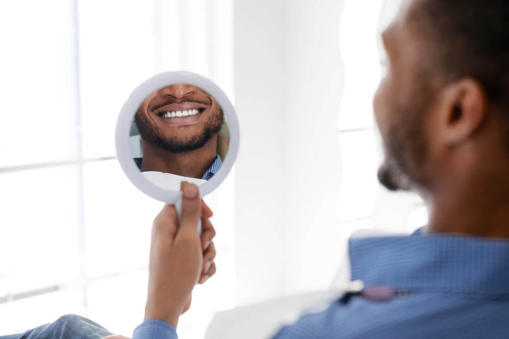 Dental patient checking his teeth in the mirror after dental cleanings